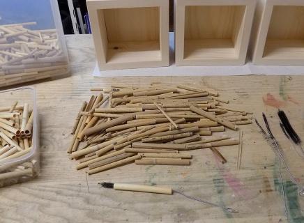 mit kleinen Bürsten werden Reet-Nistülsen Rohlinge durchgeputzt/durchgängig gemacht